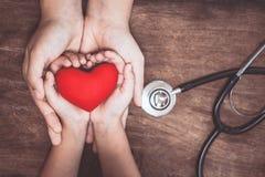 Cuore rosso sulle mani del bambino e della donna e con lo stetoscopio del ` s di medico Fotografie Stock Libere da Diritti