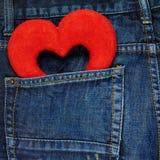 Cuore rosso in una tasca posteriore dell'jeans Fotografia Stock
