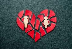Cuore rotto rosso di carta con le figure di legno dell'uomo e della donna sulla d immagine stock