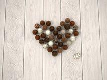 Cuore sul pavimento di legno bianco - vista superiore delle uova di Pasqua del cioccolato Immagini Stock