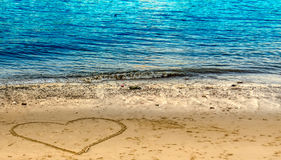 Cuore tirato sulla spiaggia Fotografie Stock