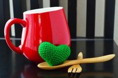Cuore verde con il cucchiaio di legno e forcella davanti alla tazza rossa fotografia stock