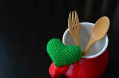 Cuore verde con il cucchiaio e forcella in tazza rossa fotografie stock