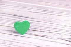 Cuore verde di feltro su un fondo di legno grigio bianco Giorno del biglietto di S Cartolina d'auguri Nozze, Immagini Stock