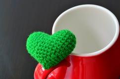 Cuore verde e tazza rossa immagine stock