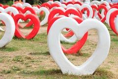Cuori bianchi e rossi su terra per il giorno di S. Valentino Fotografia Stock