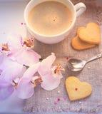 Cuori, biglietto di S. Valentino, biscotti, orchidea e una tazza di caffè tinto Immagine Stock