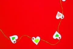 Cuori collegati in una fila, il giusto angolo più basso, su un fondo rosso Fotografia Stock Libera da Diritti