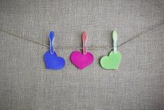 Cuori colorati su una corda su un fondo di burlap_ Immagine Stock