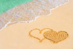 Cuori connessi dissipanti sulla spiaggia Fotografie Stock