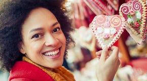 Cuori d'acquisto del pan di zenzero della bella donna in negozio di regalo Fotografia Stock Libera da Diritti
