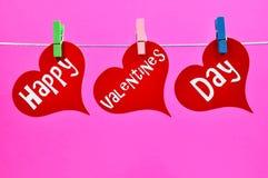 Cuori d'attaccatura di giorno variopinto del biglietto di S. Valentino felice immagini stock