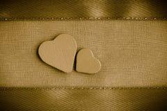 Cuori decorativi di legno del biglietto di S. Valentino sul fondo dorato del panno Immagini Stock Libere da Diritti