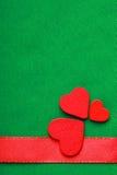 Cuori decorativi di legno rossi sul fondo verde del panno Fotografia Stock
