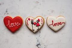 Cuori dei biscotti con amore bianco e rosso della glassa per il giorno del ` s del biglietto di S. Valentino Fotografie Stock Libere da Diritti
