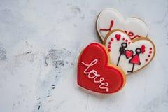 Cuori dei biscotti con amore bianco e rosso della glassa per il giorno del ` s del biglietto di S. Valentino Fotografie Stock
