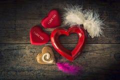 Cuori del biglietto di S. Valentino dei materiali differenti su una parte posteriore di legno d'annata Fotografia Stock