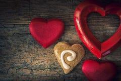 Cuori del biglietto di S. Valentino dei materiali differenti su una parte posteriore di legno d'annata Immagini Stock
