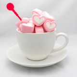 Cuori della caramella gommosa e molle in tazza su bianco Fotografie Stock