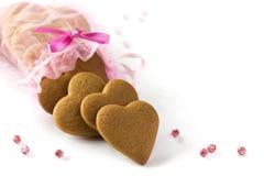 Cuori dello zenzero per il biglietto di S. Valentino e giorno delle nozze nella borsa rosa del regalo. Immagine Stock