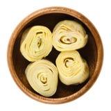 Cuori di carciofo in ciotola di legno sopra bianco Immagine Stock