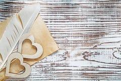 Cuori di legno della vecchia piuma di carta dello strato sul celebr di legno d'annata del bordo Fotografie Stock Libere da Diritti