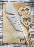 Cuori di legno della vecchia piuma di carta dello strato sul holida di legno d'annata del bordo Immagine Stock