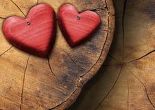 Cuori di legno rossi sulla sezione del tronco fotografie stock libere da diritti