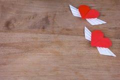 Cuori di origami con le ali su un fondo di legno Fotografia Stock Libera da Diritti