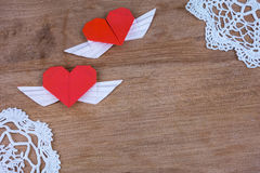 Cuori di origami con le ali su un fondo di legno con pizzo Fotografia Stock