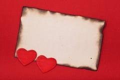 Cuori e documento in bianco bruciato Fotografia Stock