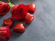 Cuori e rose rosse del cioccolato su un fondo grigio fotografia stock