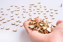 Cuori marroni d'annata che cadono da una mano fotografie stock