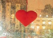 Cuori molli del giocattolo che appendono su un vetro bagnato da pioggia nella sera fotografie stock
