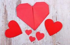 Cuori rossi del biglietto di S. Valentino sulla vecchia superficie di legno di bianco, simbolo di amore Immagini Stock Libere da Diritti