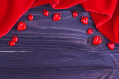 Cuori rossi del fondo elegante di giorno del ` s del biglietto di S. Valentino e tessuto rosso su fondo di legno Fotografia Stock
