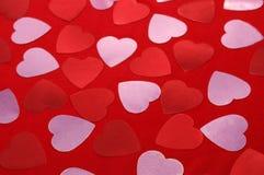 Cuori rossi e rosa sui tessuti rossi Priorità bassa del biglietto di S Immagine Stock