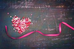 Cuori variopinti e nastri di giorno di biglietti di S. Valentino contro un backgr scuro Immagini Stock