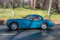 Cupé 1953 de Jaguar XK 120 que conduce en la carretera nacional Foto de archivo libre de regalías