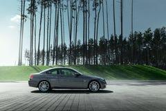 Cupé E92 de BMW del coche que se coloca en estacionamiento vacío del adoquín cerca de bosque del pino en el d3ia Foto de archivo