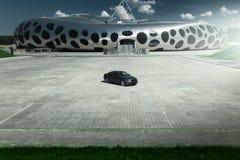 Cupé E92 de BMW del coche que se coloca en estacionamiento vacío del adoquín cerca del edificio moderno en el d3ia Foto de archivo libre de regalías