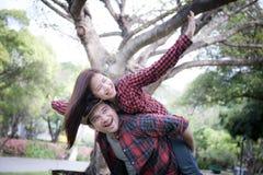 Cupé joven en parque Novio que lleva a su novia en piggyb foto de archivo
