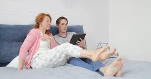 Cupê que encontra-se na cama usando o tablet pc, o homem e a mulher de Digitas falando no Internet da consultação do quarto video estoque
