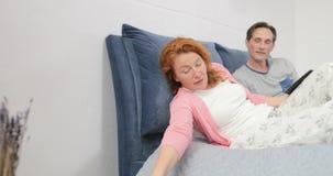 Cupê que encontra-se na cama usando a tabuleta de Digitas quando a mulher tiver o telefonema filme