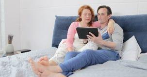 Cupê que senta-se na cama usando o tablet pc de Digitas, abraçando o homem e a mulher que falam no Internet da consultação do qua vídeos de arquivo