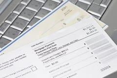 Cupón, verificación y computadora portátil del pago de hipoteca Foto de archivo