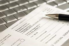 Cupón y pluma del pago de hipoteca en la computadora portátil Fotografía de archivo libre de regalías