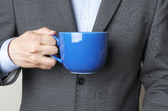 Cup. Man in a suit holding a cup Stock Photography