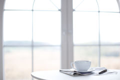 Cup. Of coffee, newspaper and pen on the table in front of window / copyspace Royalty Free Stock Photos