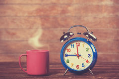 Cup and alarm clock Stock Images